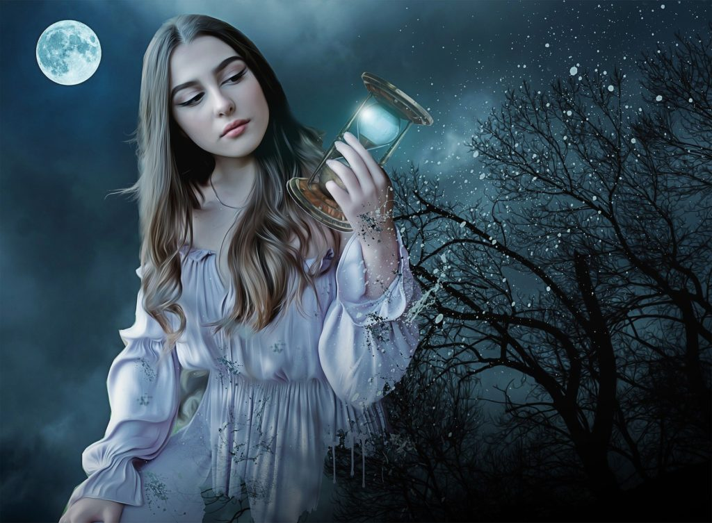 A beautiful young lady with an ancient gadget sitting in nature at night
