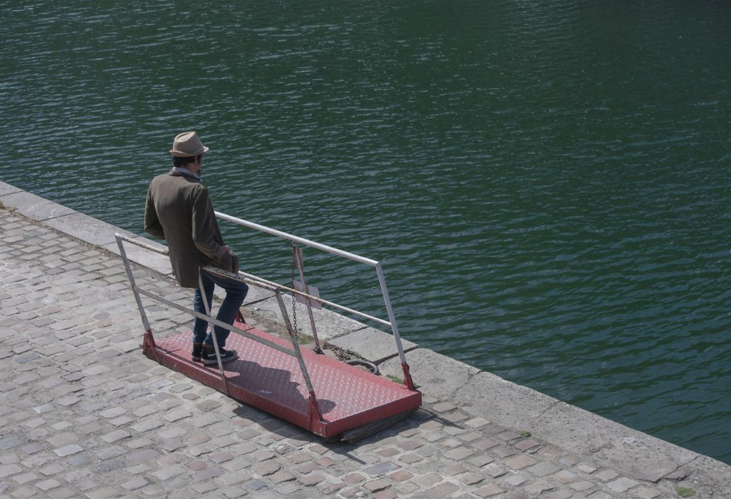 A man standing near water thinking.