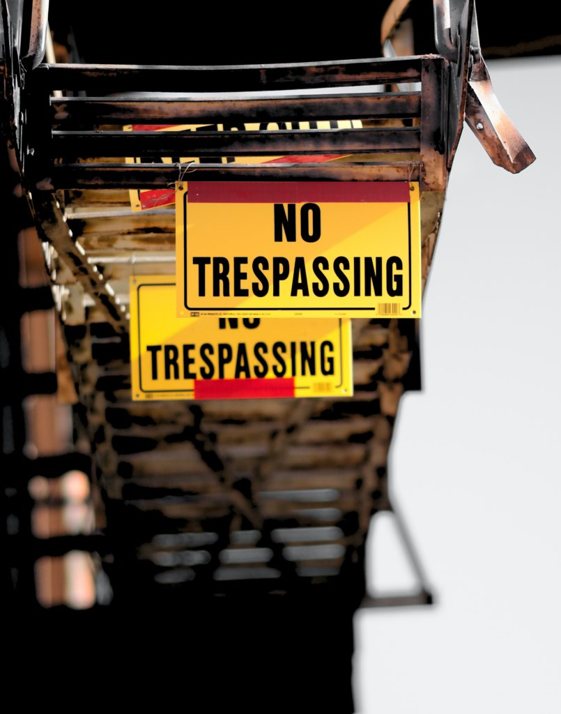 """An image of a sign board on which """"No Trespassing"""" has been written"""